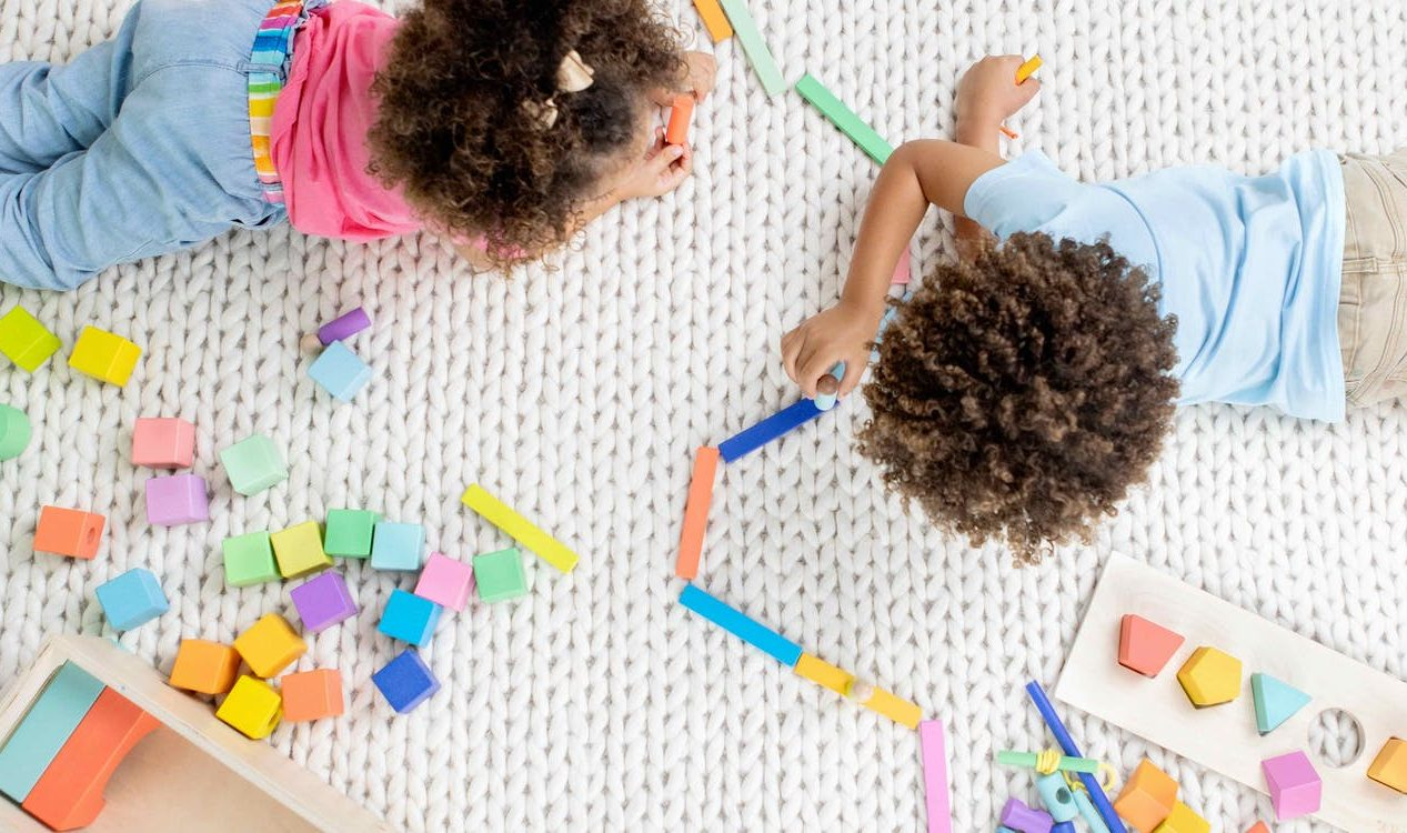 Two young children playing with the Block Set by Lovevery