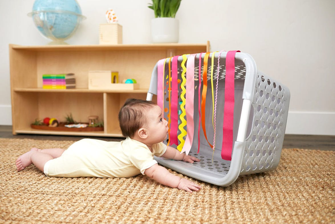 Baby doing tummy time and looking into a laundry basket with tassels hanging down