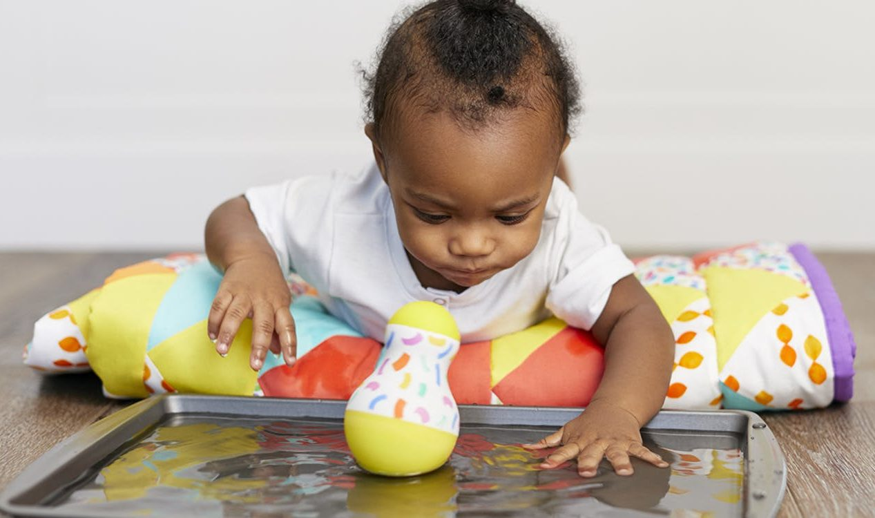 Baby practicing tummy time while looking at a Wobbler on a baking sheet with water in it