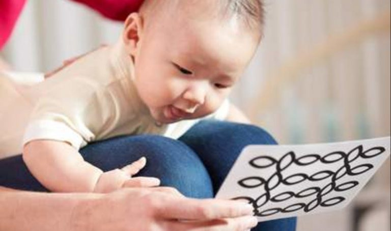 Baby doing tummy time on a woman's knees looking at Black and White cards by Lovevery