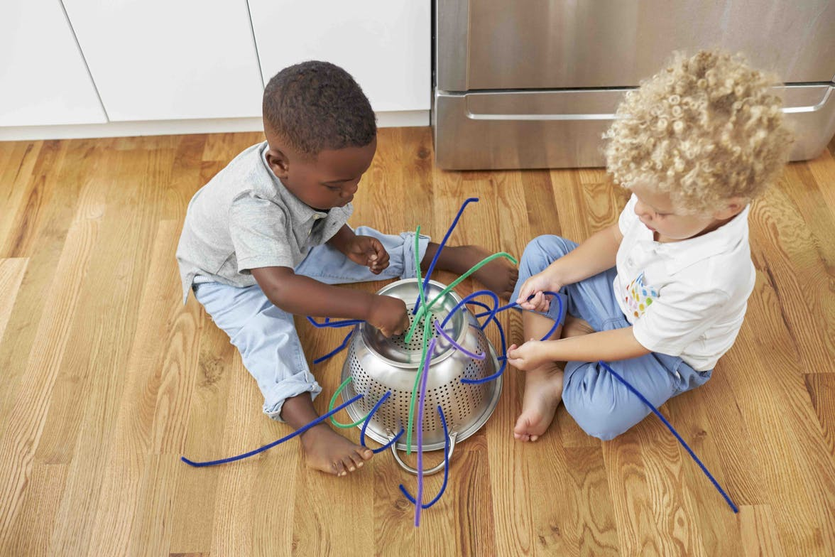 Two children putting pipe cleaners in a strainer