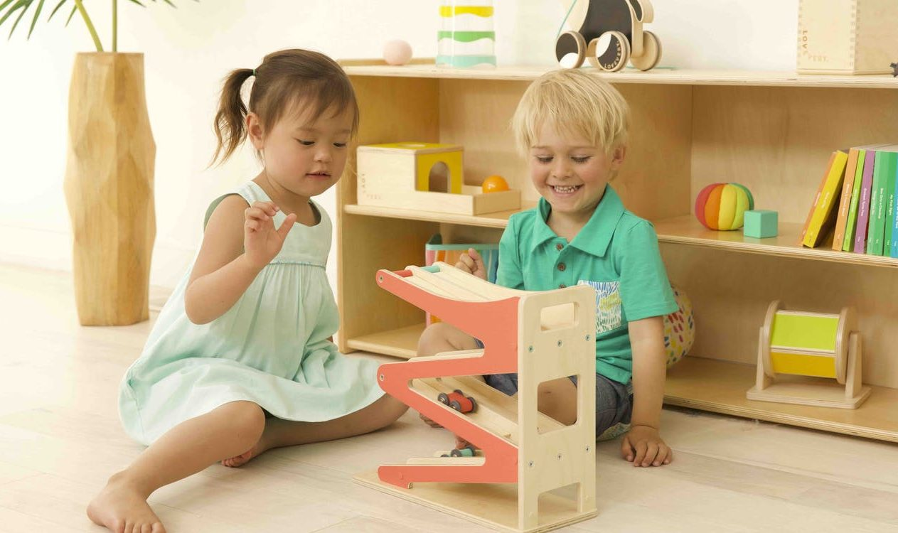 Two toddlers playing with the Race and Chase Ramp by Lovevery