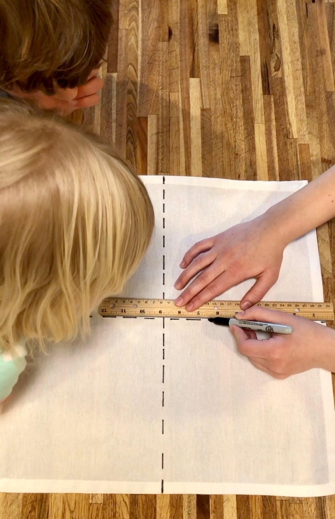 Two young children watching someone draw lines on a napkin