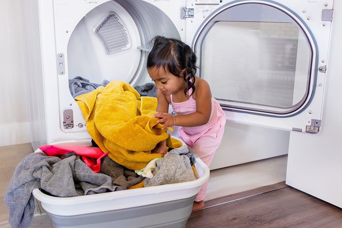 Young child helping put laundry into a washing machine