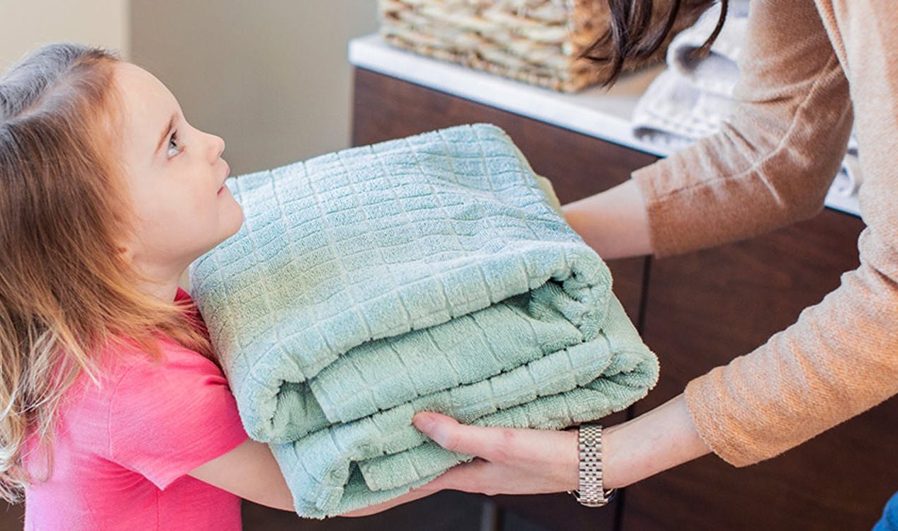 Young child being passed two folded towels