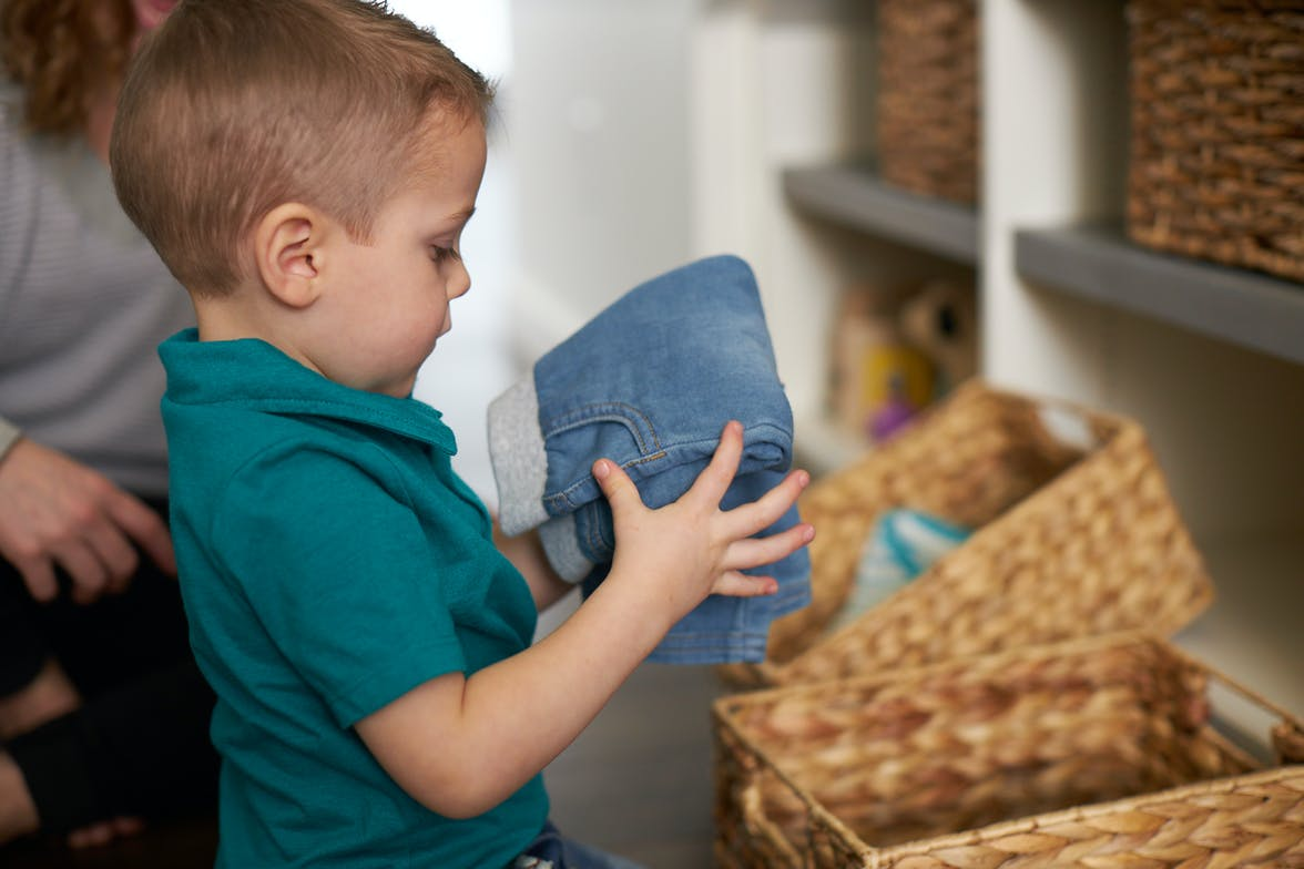 Young child putting folded jeans into a basket