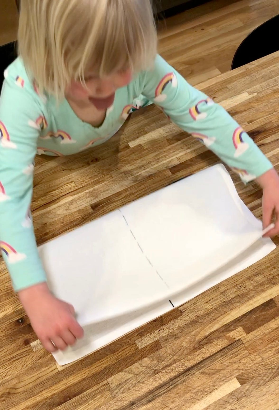 Young child folding a napkin in half