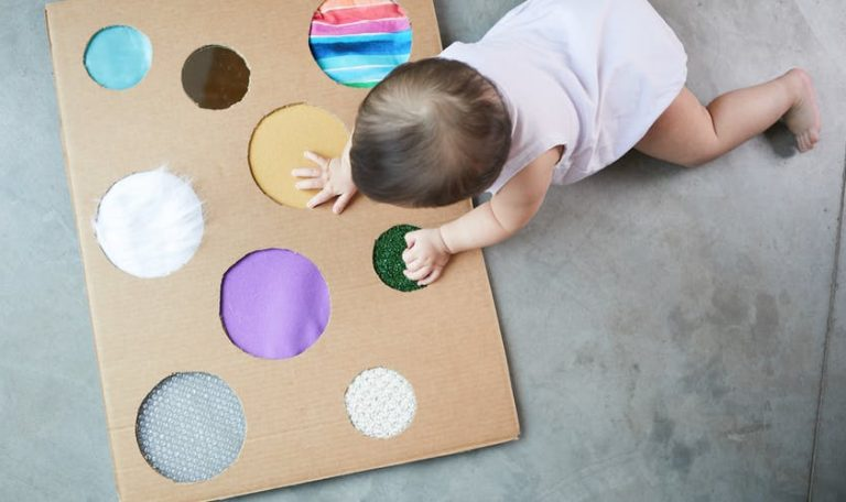 Baby touching different fabrics on a piece of cardboard