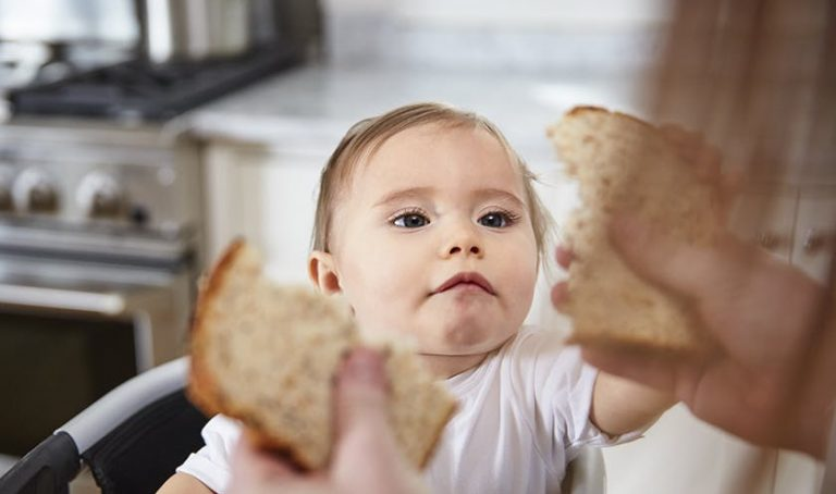 Baby looking at a woman who is holding a piece of bread