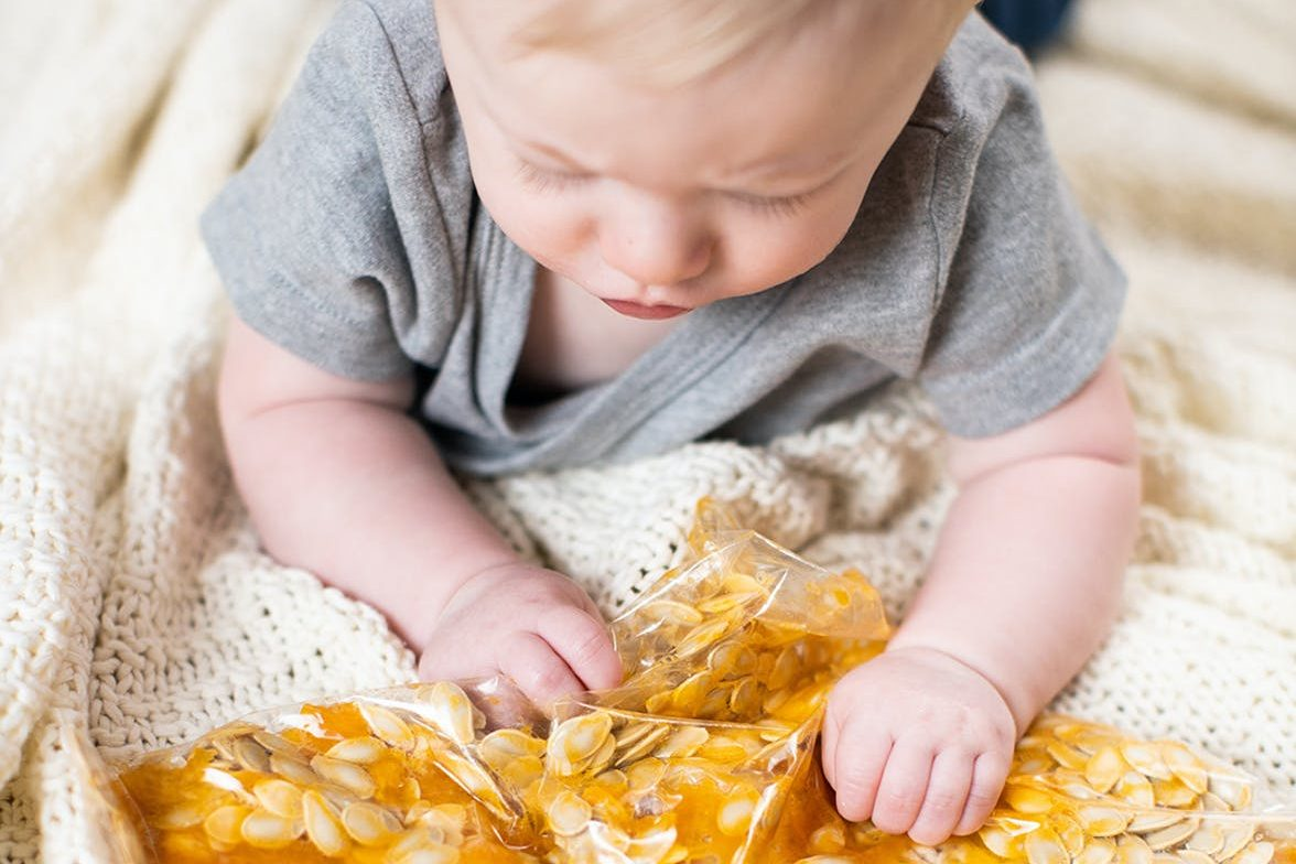 Baby playing with a plastic bag filled with pumpkin seeds