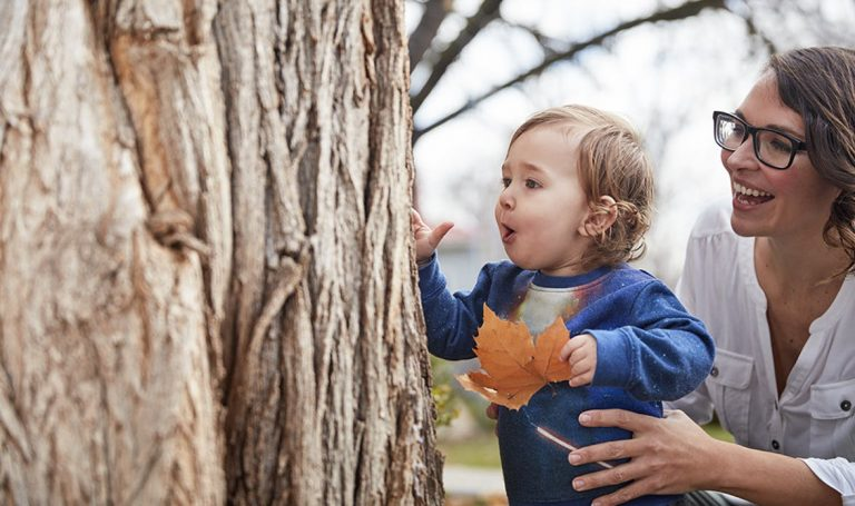 Baby outside looking at a tree being supported by a woman