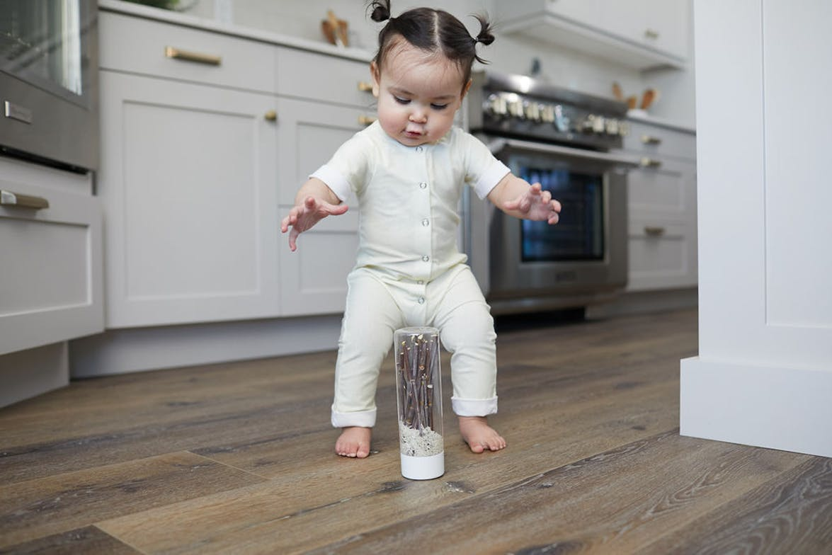 Toddler in a kitchen playing with a water bottle filled with sticks and sand