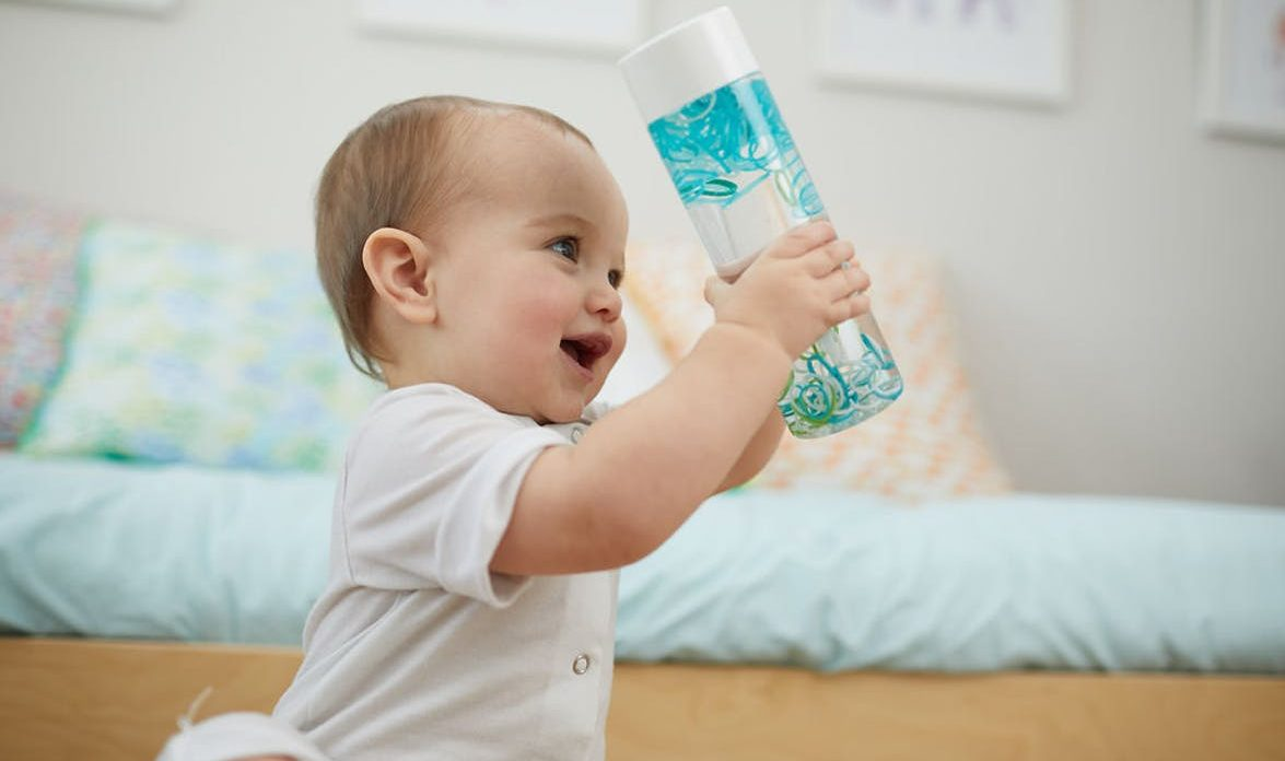Baby holding water bottle filled with water and plastic bands