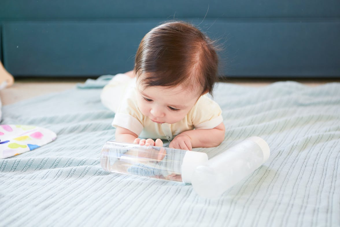 Baby playing two water bottles, one with water and one that is empty