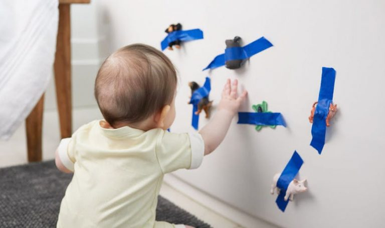 Baby looking at animal figurines that are taped to a wall