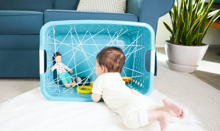Baby laying on their stomach looking at a laundry basket with their toys inside
