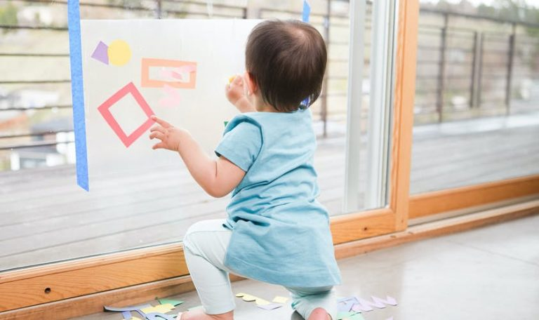 Baby playing with contact paper that's attached to a glass door