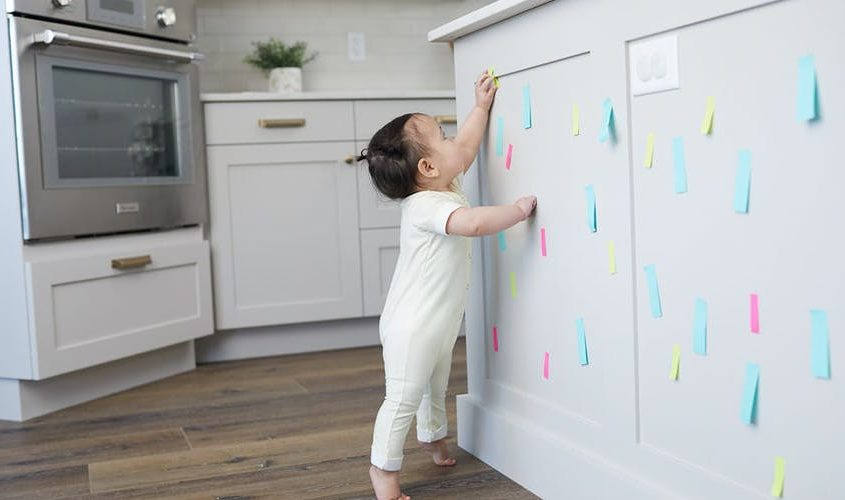 Toddler taking sticky notes off a wall