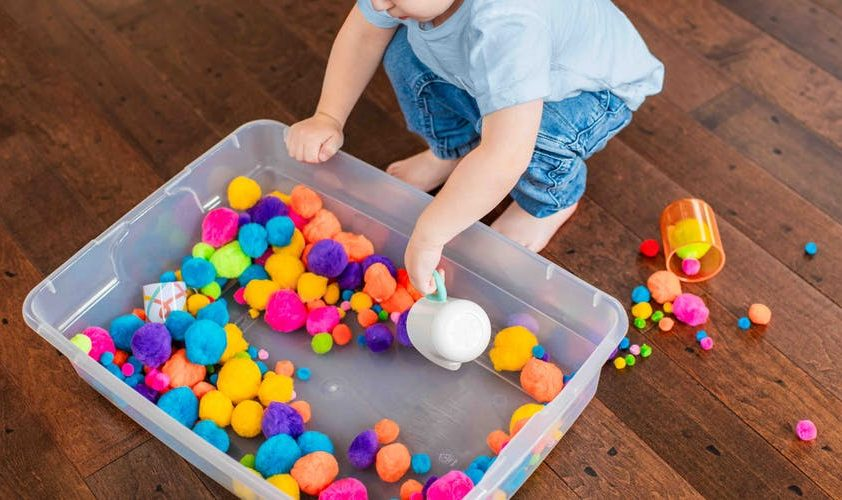 Young child using a cup to scoop up colorful pom poms