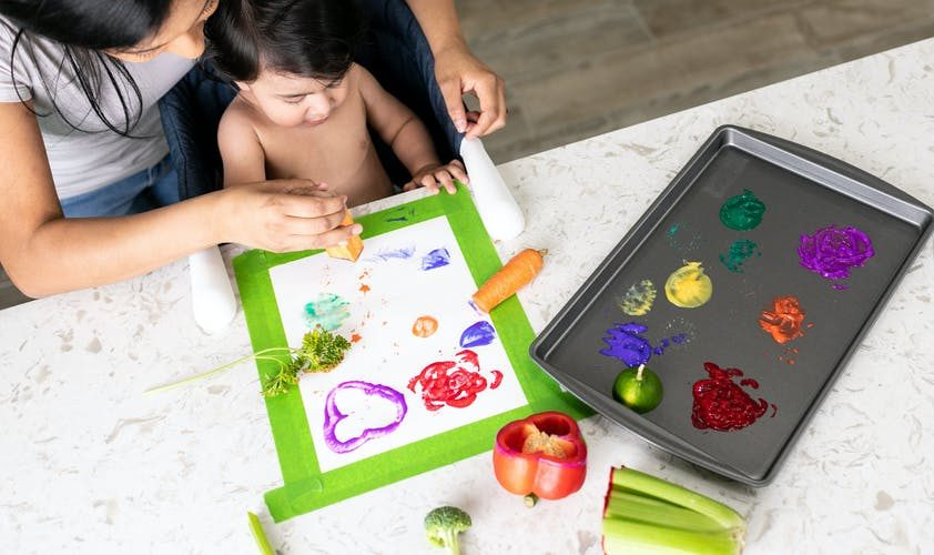 Baby painting with different kinds of vegetables