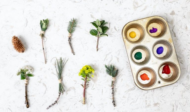 Muffin tin with paint in each section along with different plants to use as paint brushes