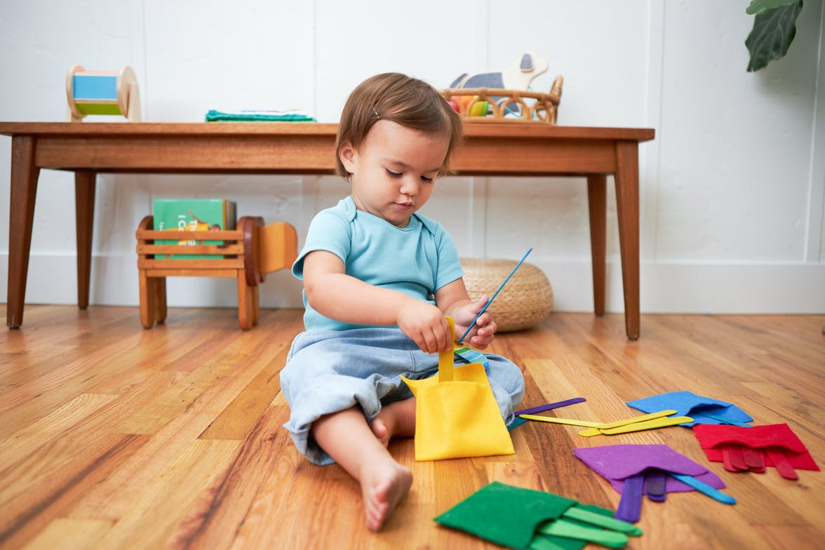 Toddler playing with colorful felt pockets and popsicle sticks