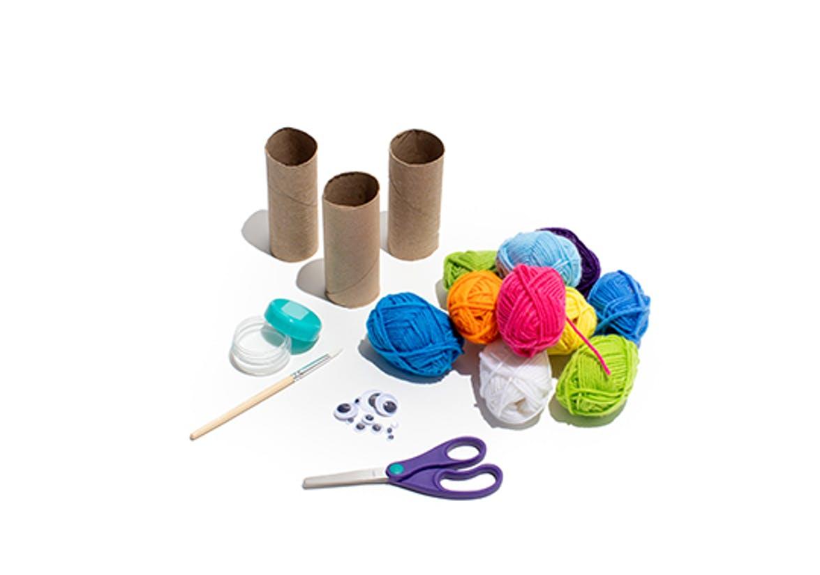 Yarn, toilet paper rolls, scissors, and googly eyes