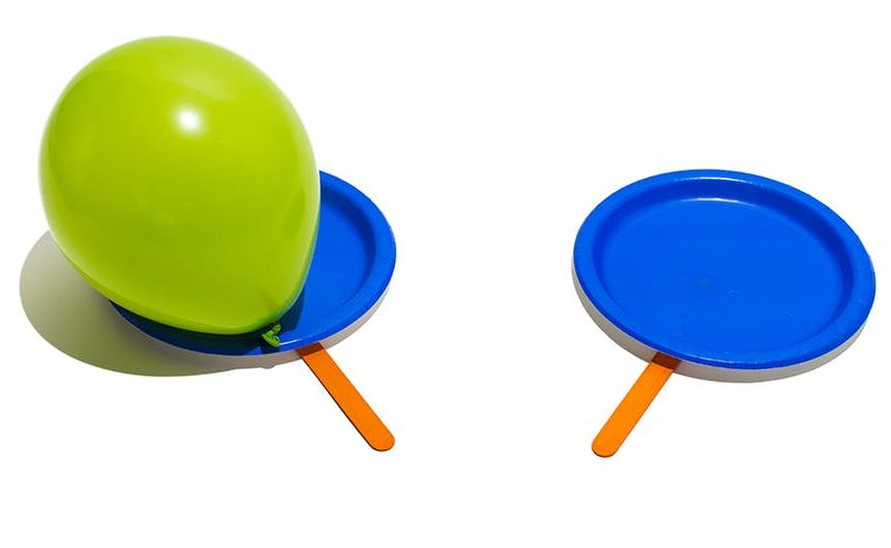 Green balloon on a blue paper plate with a wooden stick attached