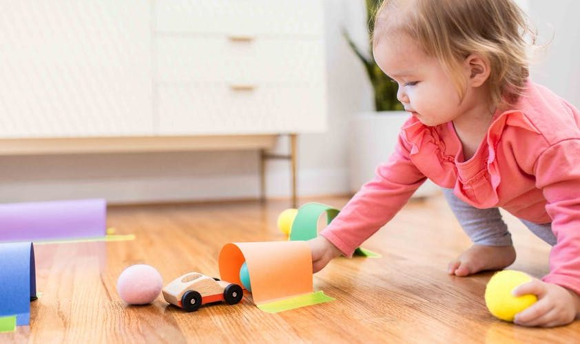 Toddler putting a ball and toy car through a DIY tunnel