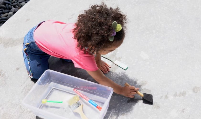 Young child painting a sidewalk with water