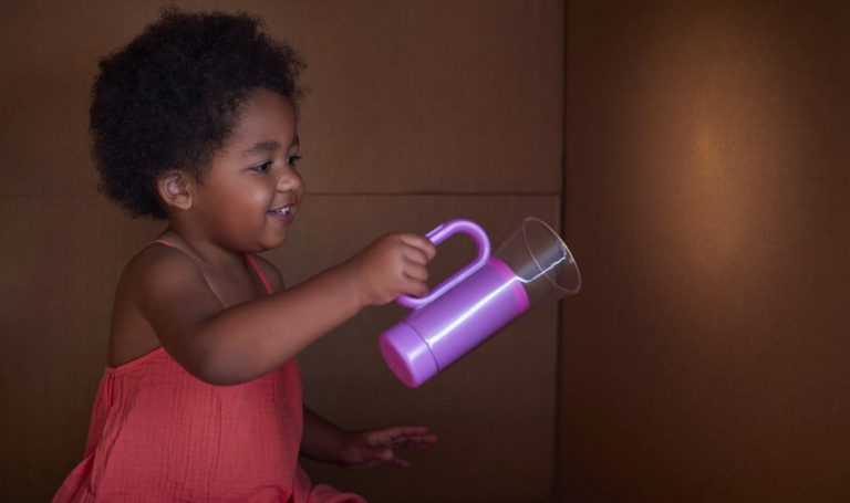 Toddler using the Lovevery flashlight against a wall