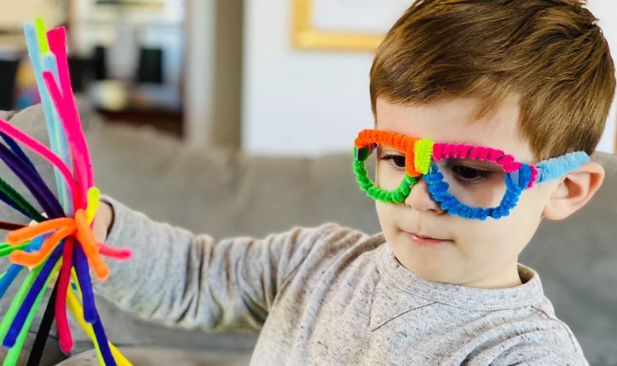 Young child wearing glasses decorated with pipe cleaners