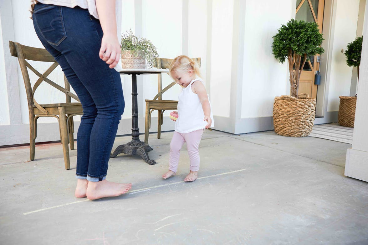 Toddler walking on a line that was drawn with chalk
