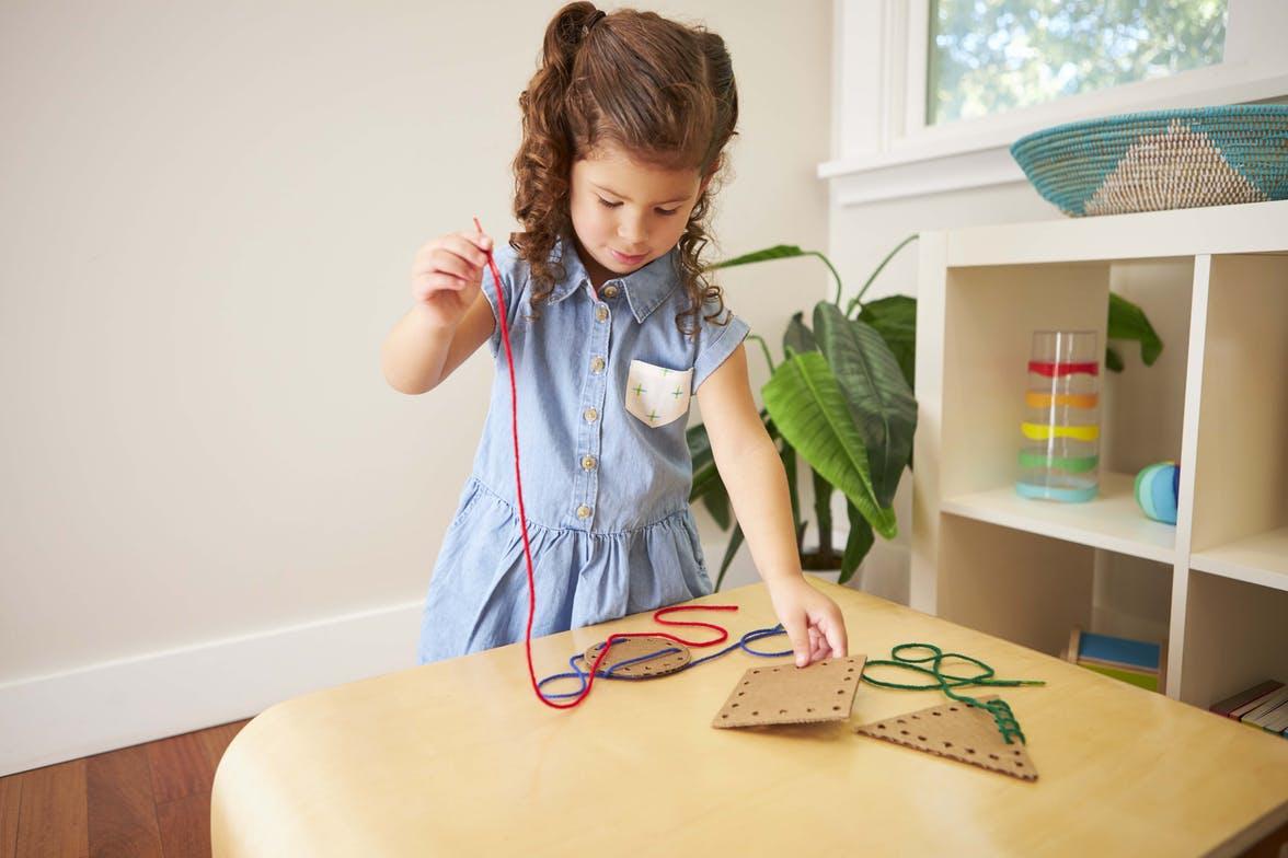 Young child stringing yarn through cardboard