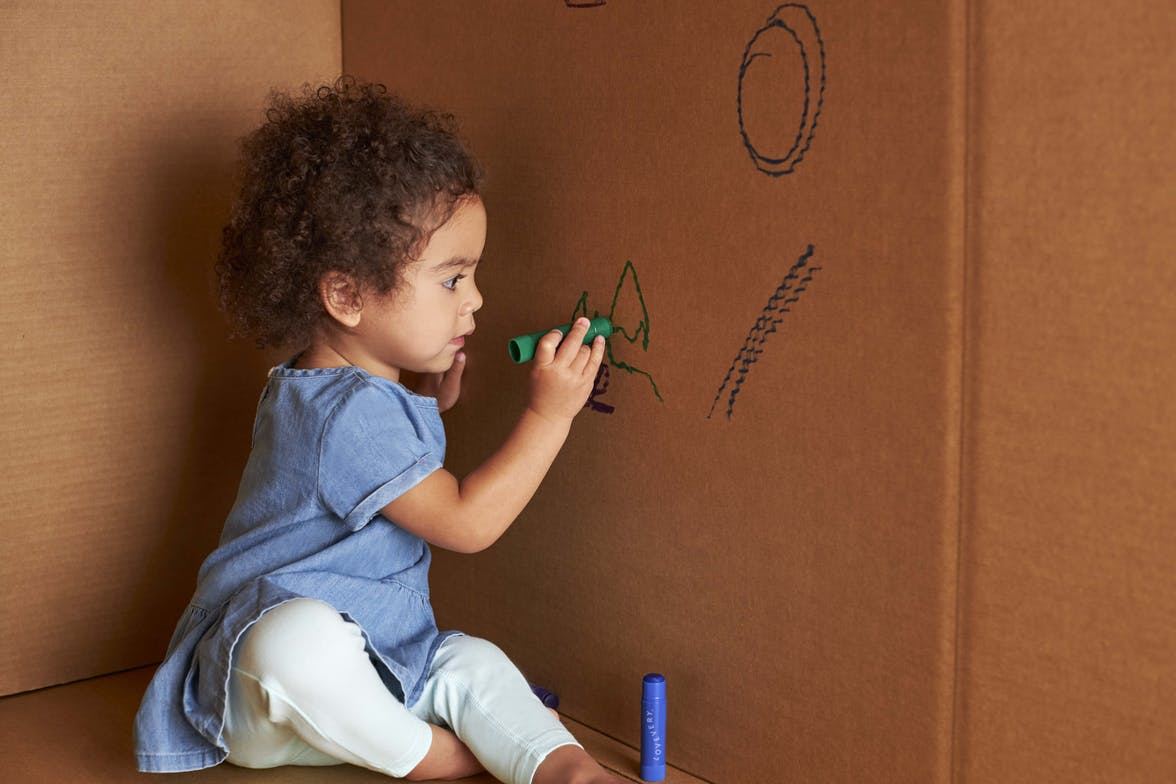 Toddler drawing on the side of a cardboard box with a marker