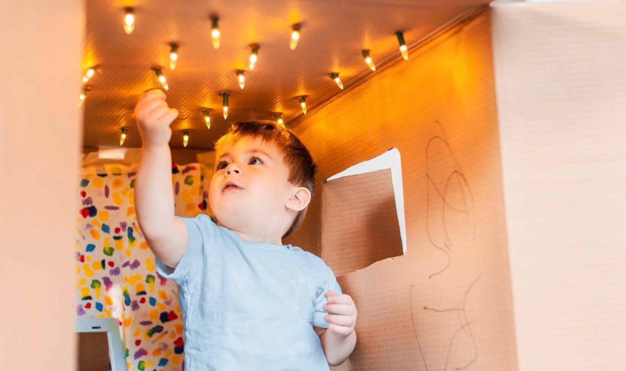 Toddler sitting in a cardboard box that has string lights at the top