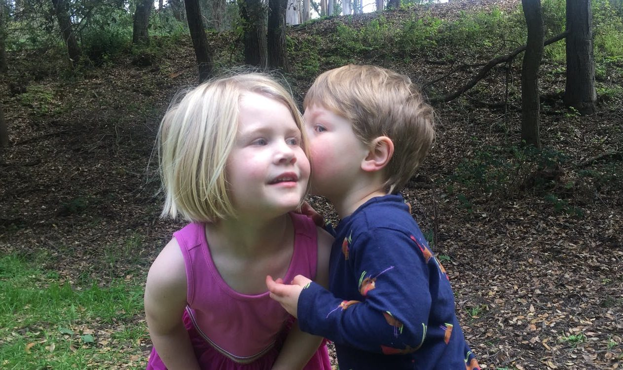 Young child whispering in another child's ear