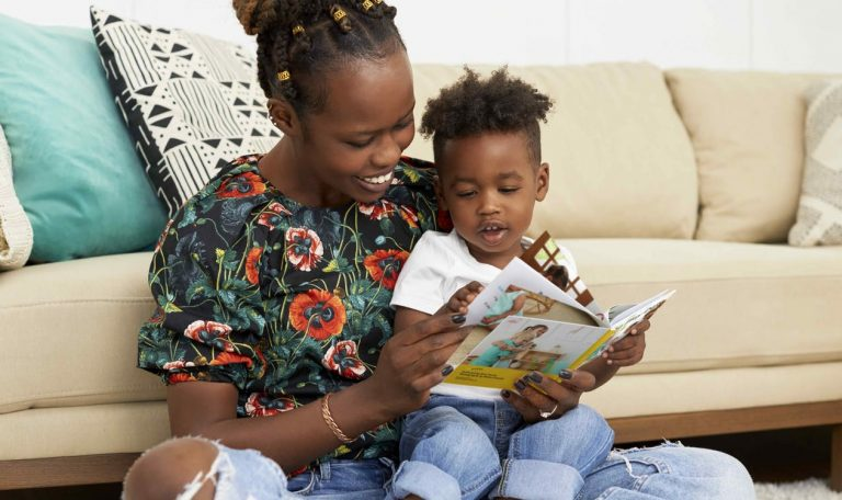 Toddler sitting on a woman's lap looking at a book
