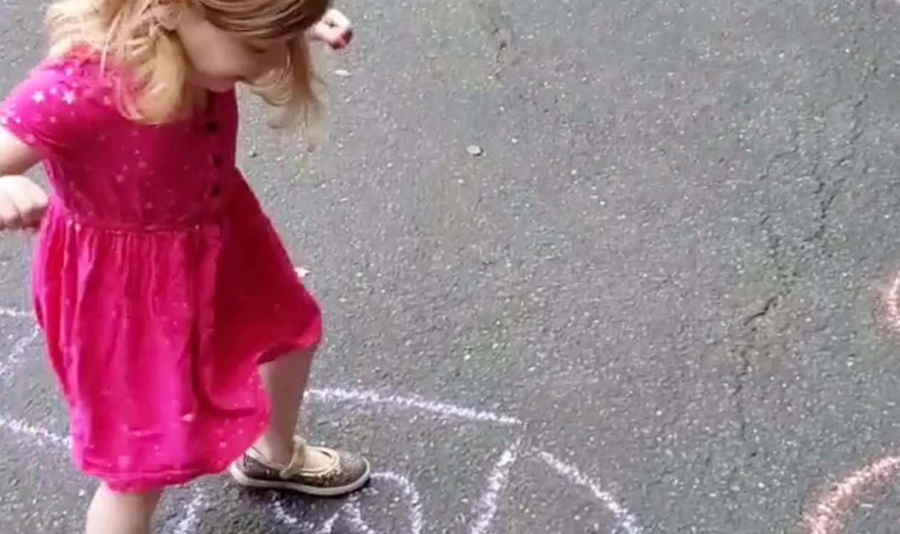 Young child playing hopscotch outside