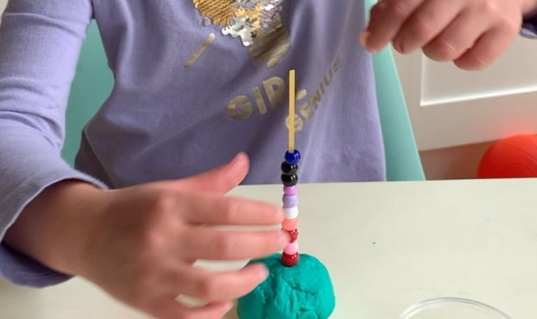 Young child putting beads on a wooden stick put in play dough