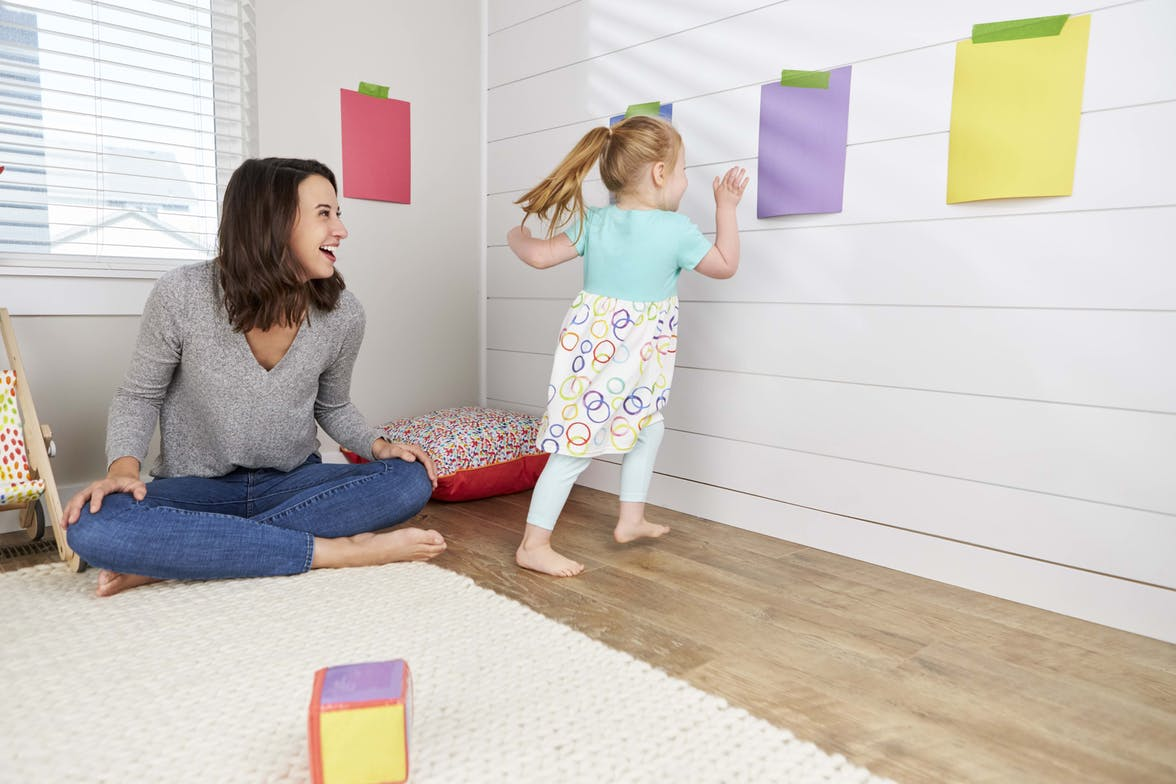 Child running to touch a purple piece of paper during a game of color tag