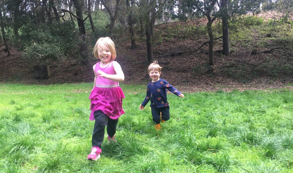 Two young children running in the grass outside