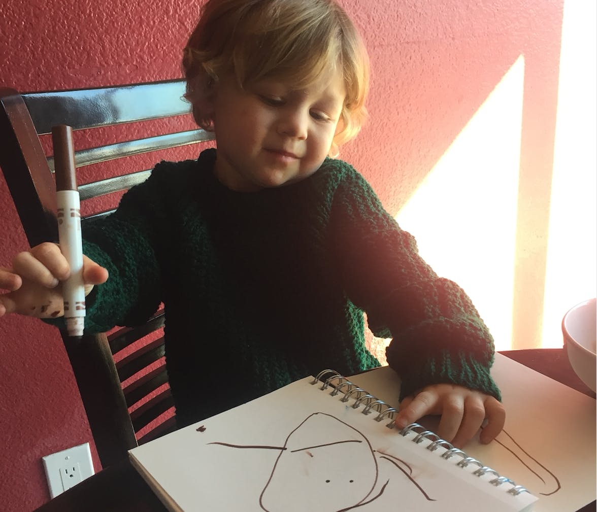A toddler with a marker in their hand drawing on paper