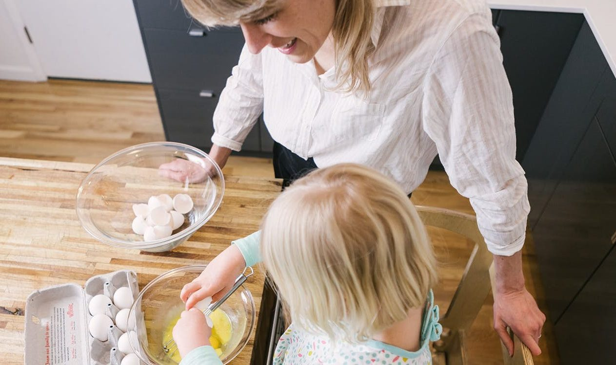 Toddler cracking an egg into a mixing bowl in the kitchen