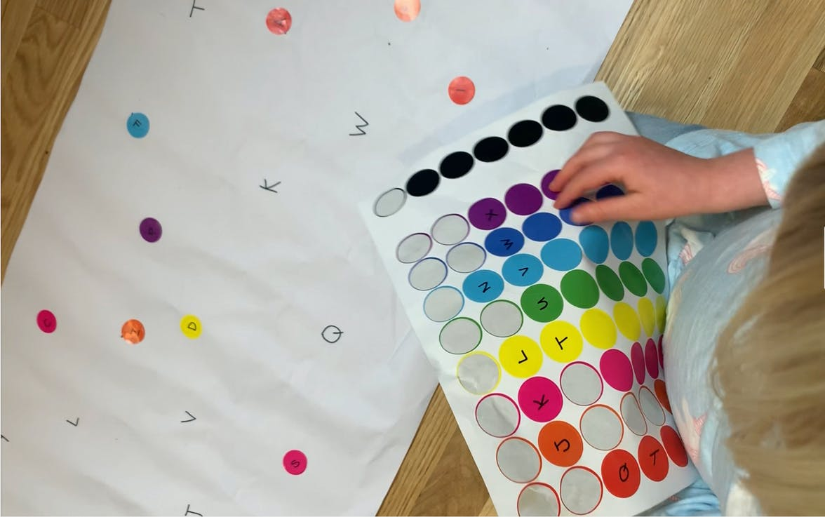 Young child putting stickers on a large piece of paper