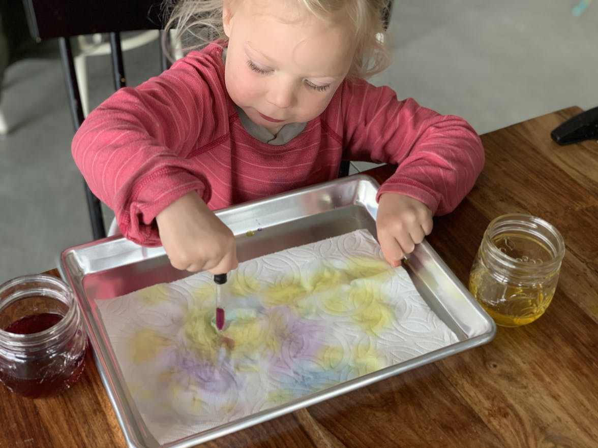 Toddler sitting with a baking sheet and a paper towel dropping colorful water on it