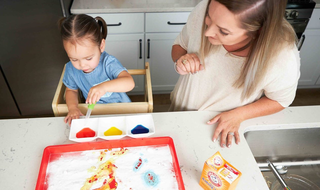 Toddler doing a STEM activity with baking soda, food coloring, and water