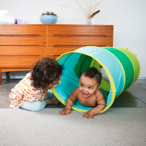 Two young children playing peek-a-boo with the Play Tunnel by Lovevery