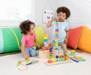 Two young children stacking blocks from The Block Set by Lovevery