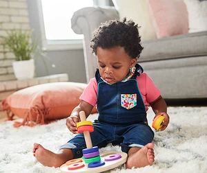 Toddler sitting up playing with the Wooden Stacker by Lovevery